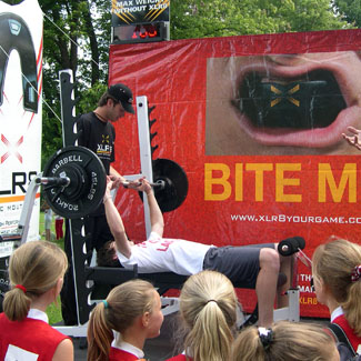 man on bench press on stage at event