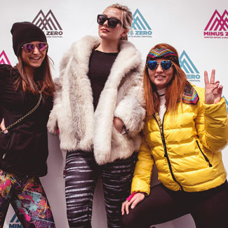 three girls posing with Minus Zero branded backdrop